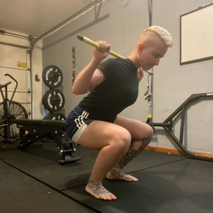 Personal Trainer, Annie back squatting using a bar.