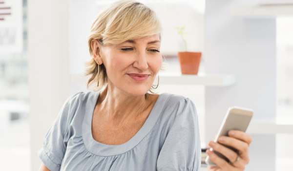 Women looking at her cell phone and smiling