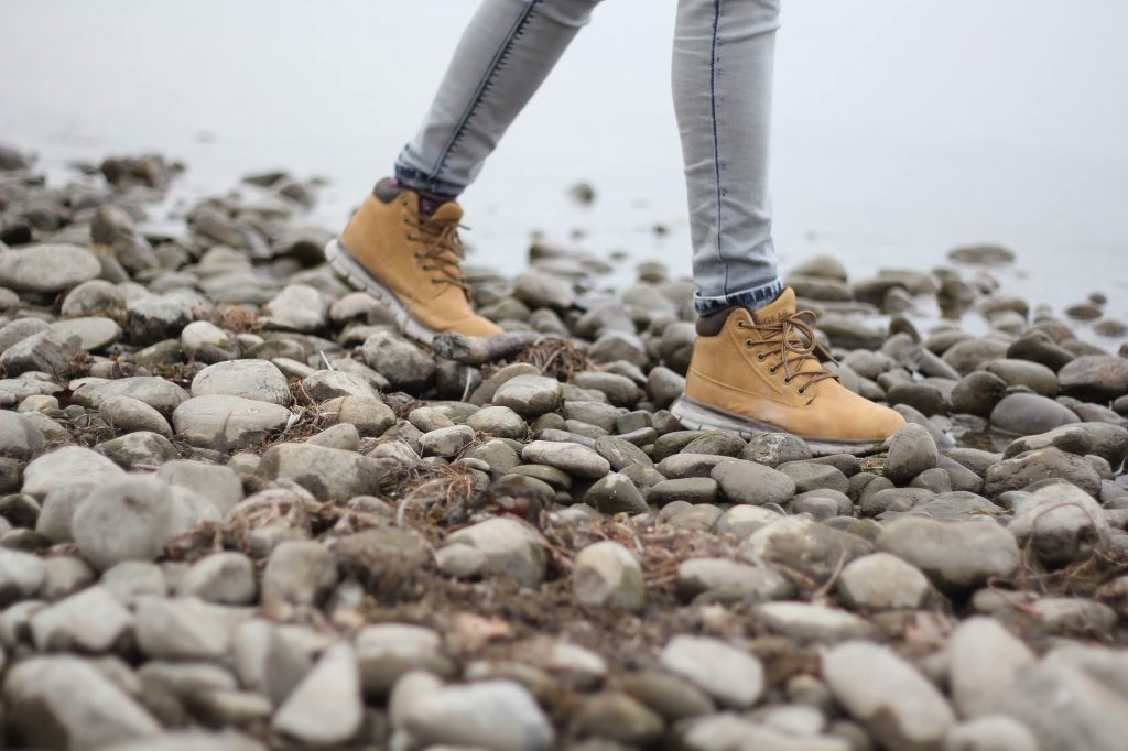 Image of individual legs and feet in hiking boots walking on rocks.
